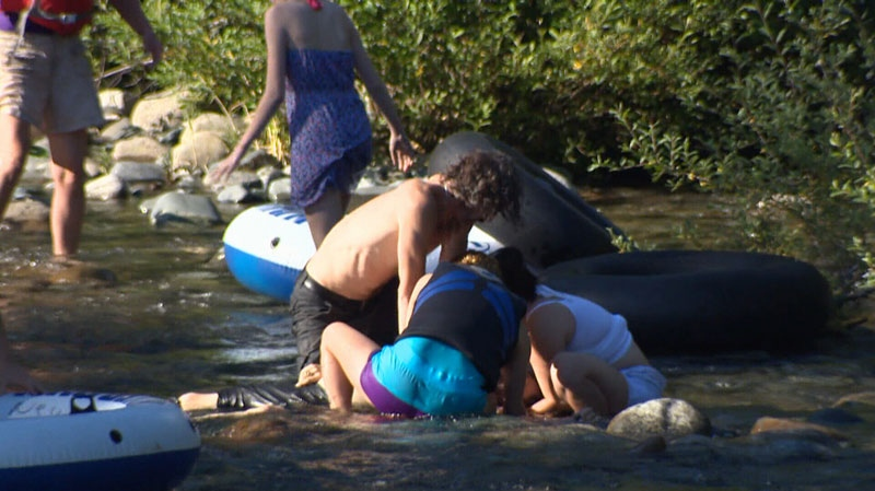 Friends try to resuscitate a 42-year-old man who fell off an inner tube on the Puntledge River Wednesday evening. July 4, 2013. (CTV)