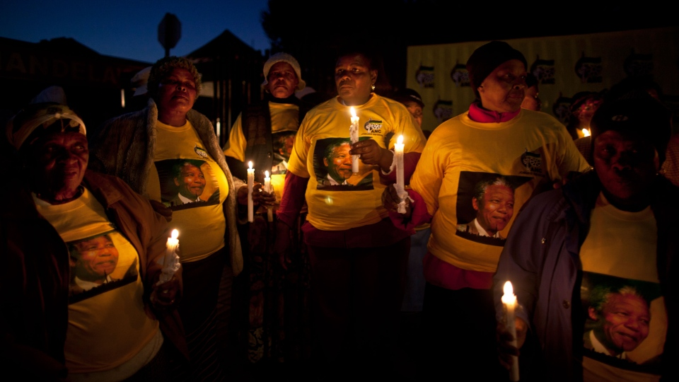 ANC women's organization members, hold candles and chant prayers to honor former South African President Nelson Mandela in front of his house in the Soweto township, on the outskirts of Johannesburg, South Africa, Thursday, July 4, 2013. (AP / Muhammed Muheisen)
