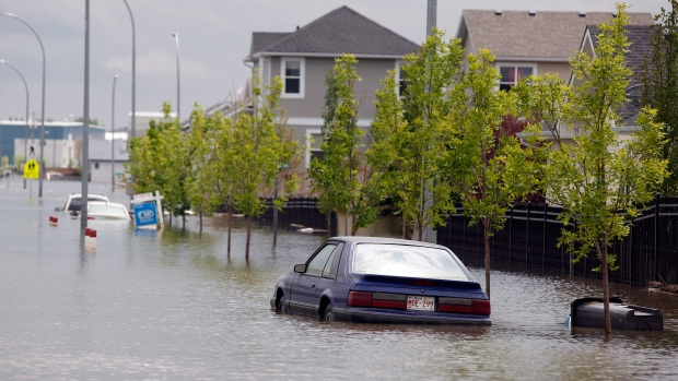 Cars sit parked in flood water in a restricted neighborhood in High River, Alta., Thursday, July 4, 2013. (Jeff McIntosh / THE CANADIAN PRESS)
