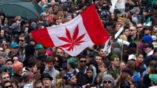 A Canadian flag with a marijuana plant on it instead of a maple leaf is carried through the crowd during a rally in downtown Vancouver, B.C., on Wednesday April 20, 2011. (Darryl Dyck / THE CANADIAN PRESS)