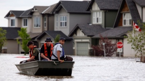 Members of the RCMP return from a boat patrol of a still flooded neighborhood in High River, Alta., Thursday, July 4, 2013. (Jeff McIntosh / THE CANADIAN PRESS)