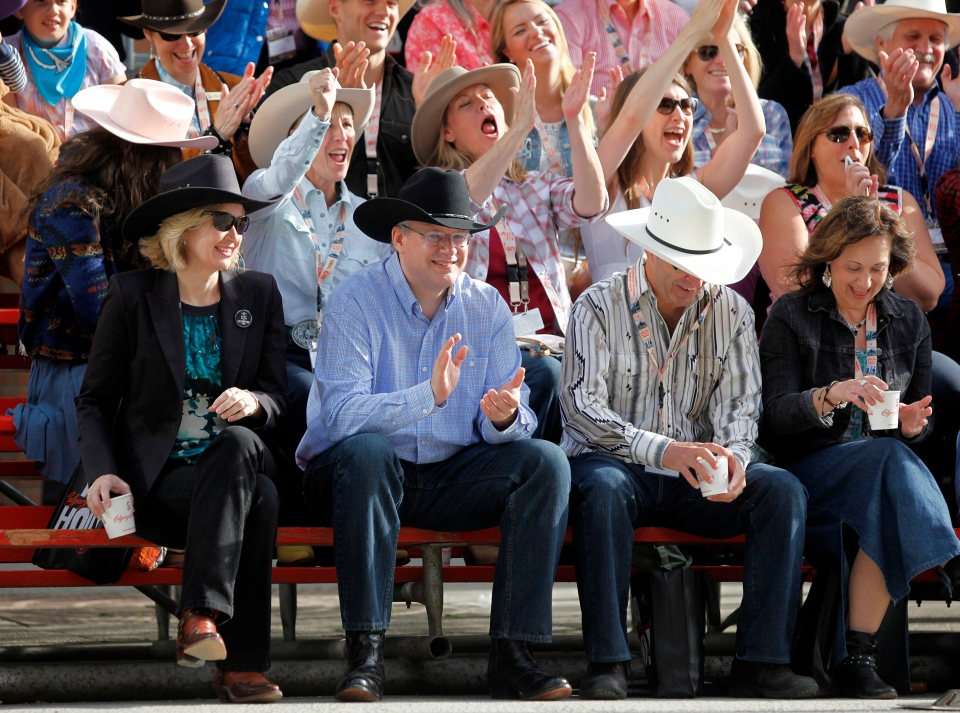 Prime Minister Stephen Harper, centre, and his with Laureen, cheer during the Calgary Stampede parade in Calgary, Friday, July 5, 2013. (Jeff McIntosh / THE CANADIAN PRESS)