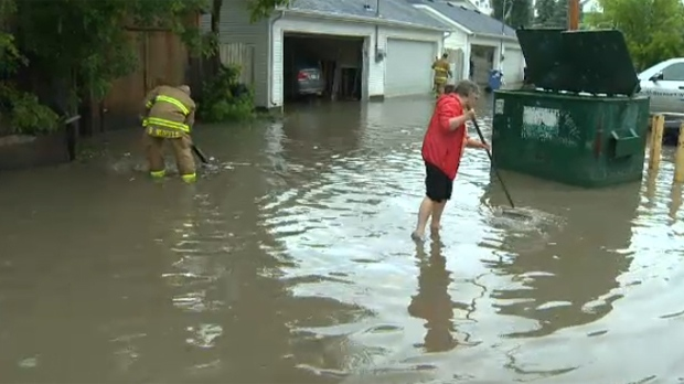 Sunnyside residents working alongside members of the Calgary Fire Department in a joint effort to remove flood waters from the neighbourhood