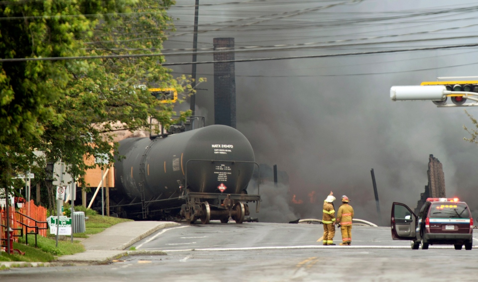 Smoke rises from railway cars that were carrying crude oil after derailing in downtown Lac Megantic, Quebec, Canada, Saturday, July 6, 2013. (Paul Chiasson / THE CANADIAN PRESS)