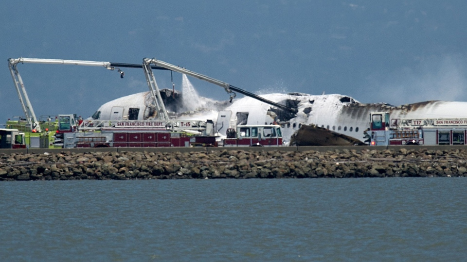 A fire truck sprays water on Asiana Flight 214 after it crashed at San Francisco International Airport on Saturday, July 6, 2013, in San Francisco. (AP / Noah Berger)