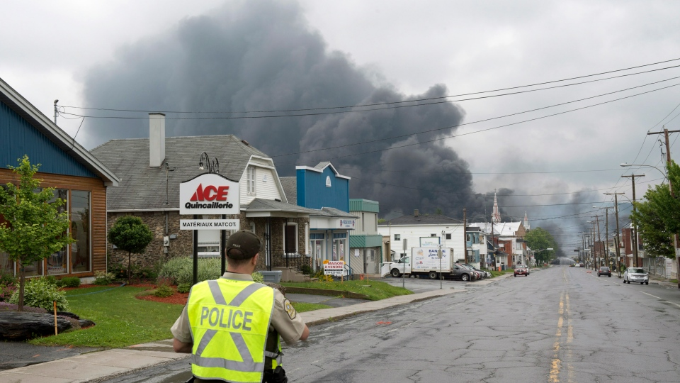 A police officer watches as smoke rises from railway cars that were carrying crude oil after derailing in downtown Lac Megantic, Que., Saturday, July 6, 2013. (Paul Chiasson/ THE CANADIAN PRESS)