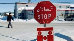 FILE -- A person walks past a stop sign displayed in both English and Inuktitut in the city of Iqaluit, Nunavut on March 28, 2009.  (THE CANADIAN PRESS/Nathan Denette)