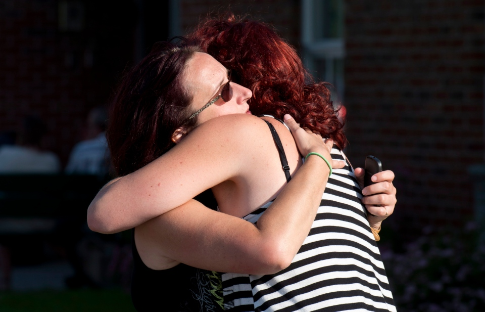 Federique Mailloux hugs a friend as they wait outside an emergency centre for news of friends following a train derailment in downtown Lac Megantic, Que., causing explosions of railway cars that were carrying crude oil Saturday, July 6, 2013. THE CANADIAN PRESS/Paul Chiasson
