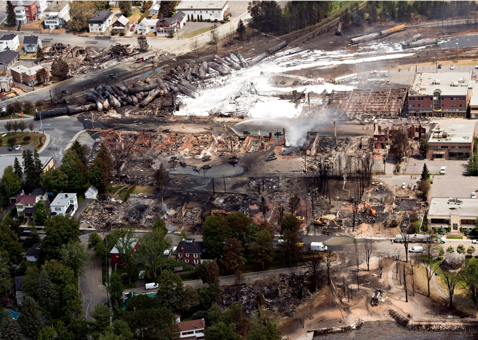 The downtown core lays in ruins as fire fighters continue to water smoldering rubble in Lac Megantic, Que., Sunday, July 7, 2013. (Ryan Remiorz / THE CANADIAN PRESS)