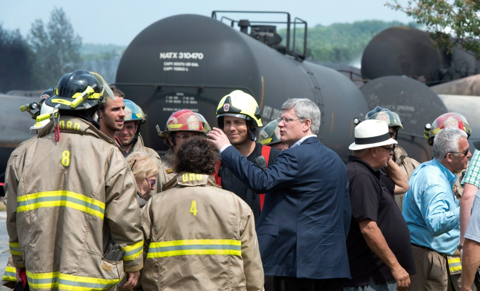 Prime Minister Stephen Harper meets with firefighters in Lac-Megantic, Que., the day after a train derailed causing explosions of railway cars carrying crude oil, Sunday, July 7, 2013. (Paul Chiasson / THE CANADIAN PRESS)
