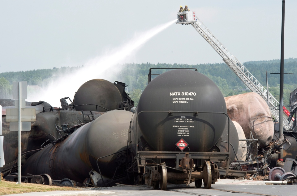 Firefighters keep watering railway cars the day after a train derailed causing explosions of railway cars carrying crude oil Sunday, July 7, 2013, in Lac Megantic, Que. (Paul Chiasson /The Canadian Press)
