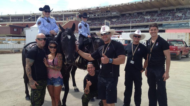 Members of The SkyHawks pose with mounted officials in the Calgary Stampede infield following an early 2013 performance (Courtesy: Facebook)
