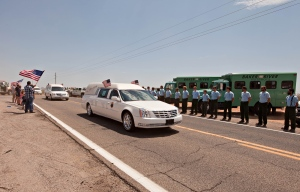 Hearses carrying the bodies of the Granite Mountain Hotshots pass by Bureau of Land Management and U.S. Forest Service Fire personnel along Highway 89. (AP/The Arizona Republic, Tom Story)