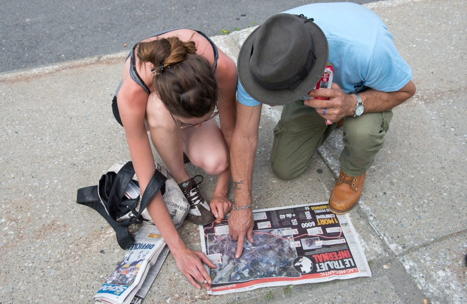 Residents look at an aerial photograph in a newspaper to try to identify buildings that were leveled when a train derailed causing explosions of railway cars carrying crude oil in Lac-Megantic, Que., Sunday, July 7, 2013. (Paul Chiasson / THE CANADIAN PRESS)