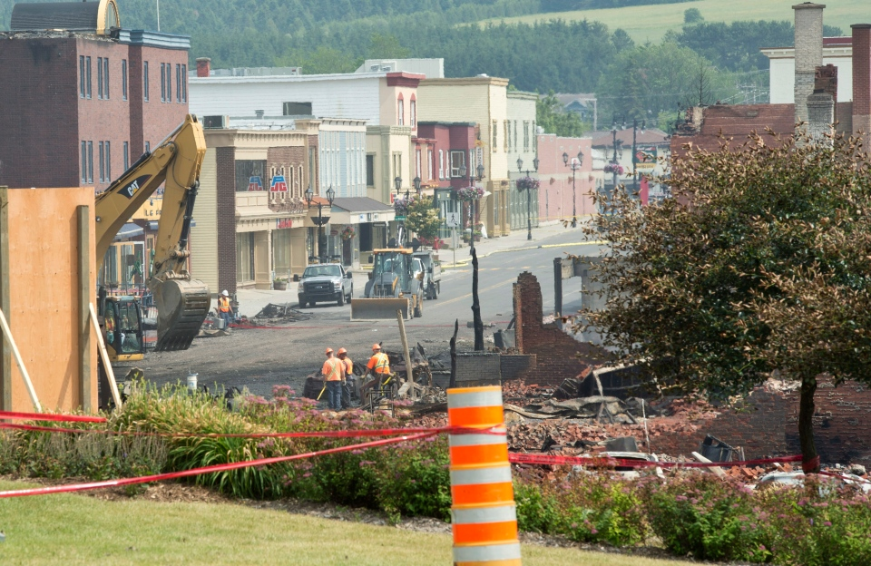 A leveled building is seen in the foreground the day after a train derailed causing explosions of railway cars carrying crude oil Sunday, July 7, 2013, in Lac Megantic, Que. (The Canadian Press/Paul Chiasson)
