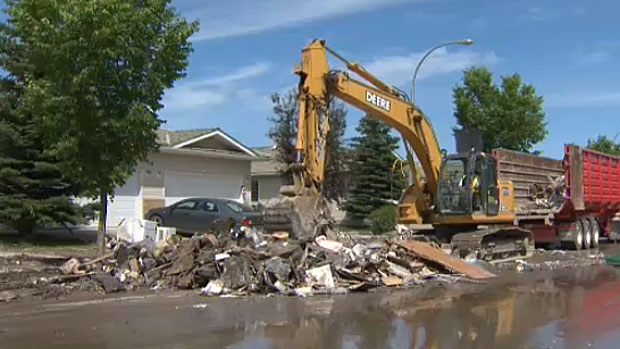 Heavy machinery has been brought in to help clear the mass of flood-damaged debris that was pulled out of peoples homes in High River.