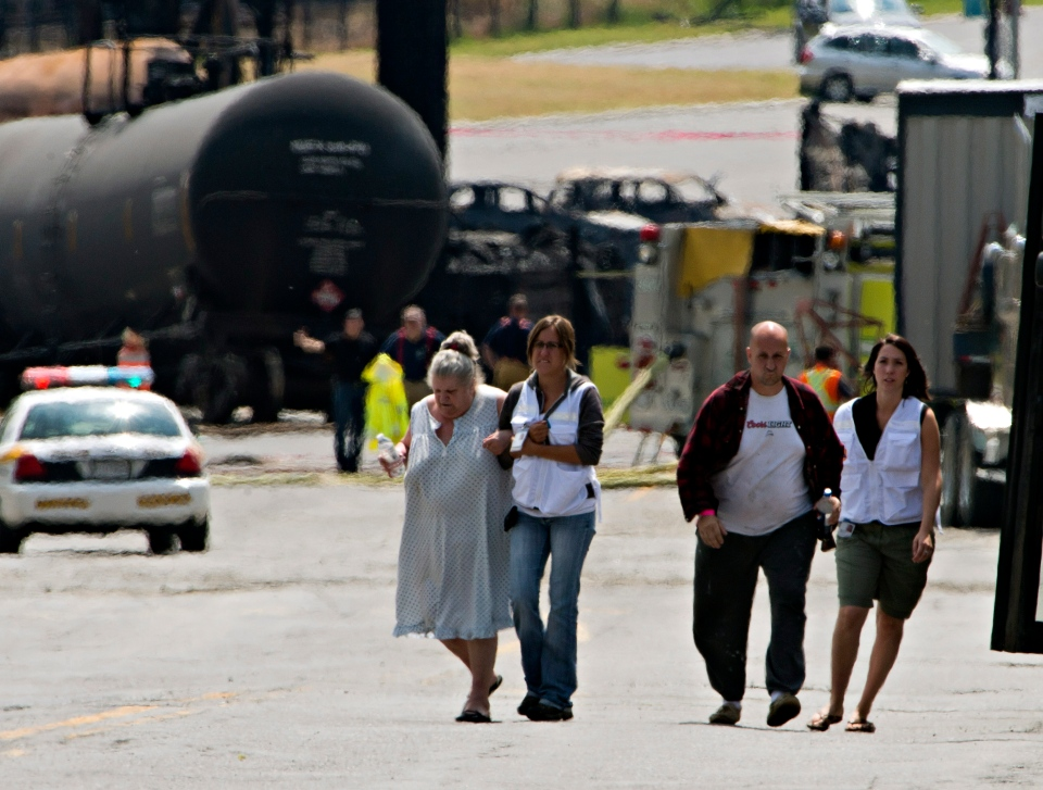Volunteers escort evacuees to their home near the blast site to pick up some belongings,  in Lac-Megantic, Que. Monday, July 8, 2013. (Ryan Remiorz / THE CANADIAN PRESS)