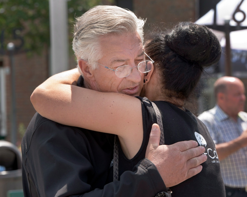 Raymond Lafontaine, who lost a son and two daughters-in-law, hugs Maud Verrault, who worked at the Music-Cafe Bar and lost friends and colleagues, at the refugee centre in Lac-Megantic, Que., Monday, July 8, 2013. (Ryan Remiorz / THE CANADIAN PRESS)