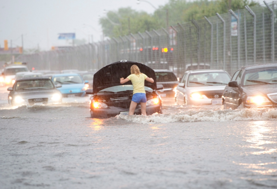 A woman checks her car in flood water on Lakeshore West during a storm in Toronto on Monday, July 8, 2013. (Frank Gunn / THE CANADIAN PRESS)