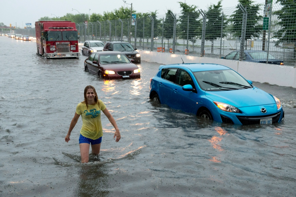 A woman wades through flood water on Lakeshore West during a storm in Toronto on Monday, July 8, 2013. (Frank Gunn  / THE CANADIAN PRESS)