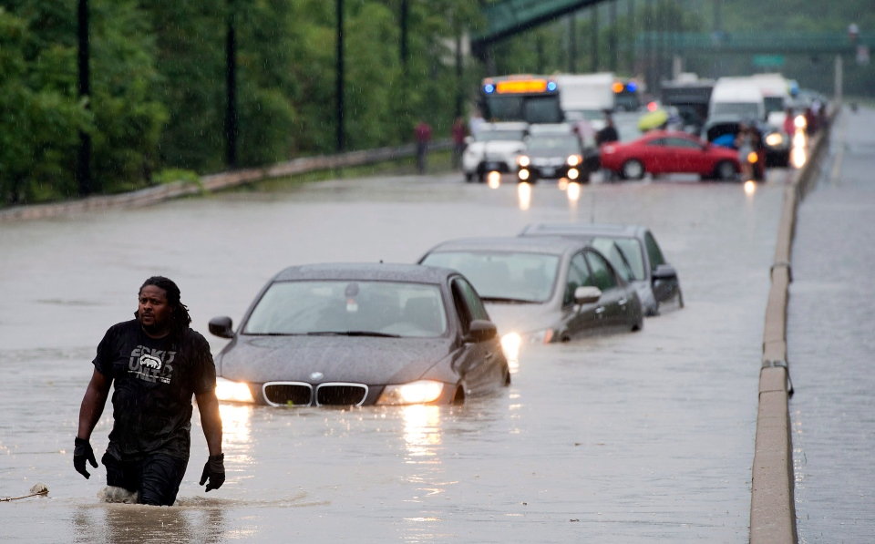 A tow truck driver walks back through flood waters after hooking up a car on the Don Valley Parkway in Toronto on Monday, July 8 2013. (THE CANADIAN PRESS)