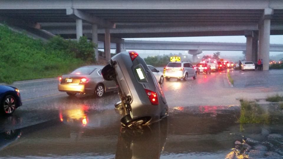 A car is partially submerged on Highway 427 in Toronto on Monday, July 8, 2013. (Jorge Costa)