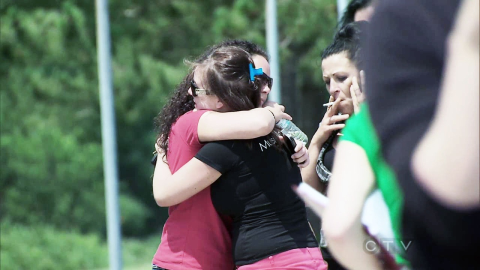 Residents in Lac-Megantic react after hearing the latest on the train derailment Monday, July 8, 2013.
