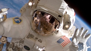 In this file photo, an American astronaut waves during a spacewalk outside the International Space Station in July 2007. (NASA)