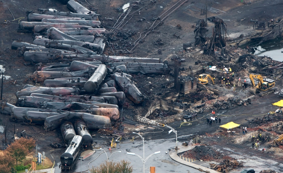 Workers comb through the debris after a train derailed causing explosions of railway cars carrying crude oil in Lac-Megantic, Que., Tuesday, July 9, 2013. (Paul Chiasson / THE CANADIAN PRESS)