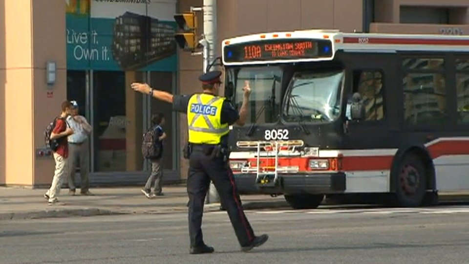 A police officer directs traffic due to a power outage near Islington Ave. and Bloor St., Wednesday, July 10, 2013.