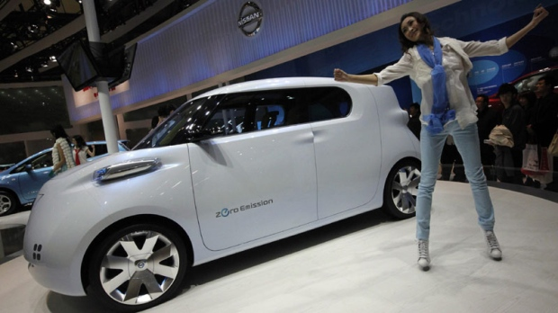 An artist performs next to a Nissan Townpod at the Shanghai International Auto Show Thursday, April 21, 2011 in Shanghai, China. (AP Photo/Eugene Hoshiko)