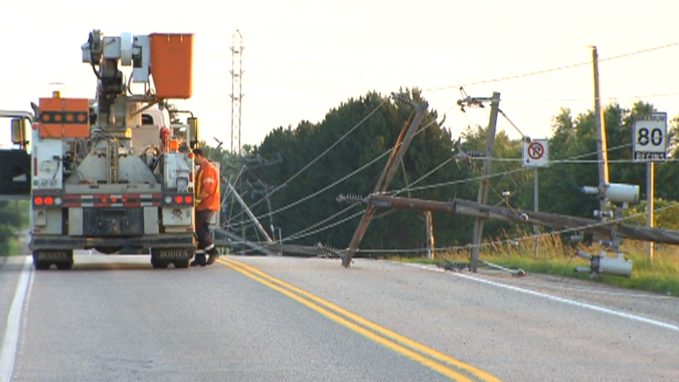Crews work to repair a number of hydro poles that were knocked down during a storm in Guelph, Ont., Wednesday, July 10, 2013.