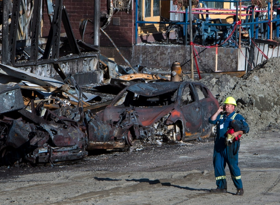 A worker walks through the crash site Thursday, July 11, 2013 in Lac-Megantic, Quebec after a train derailed ignited tanker cars carrying crude oil. (THE CANADIAN PRESS/Ryan Remiorz)