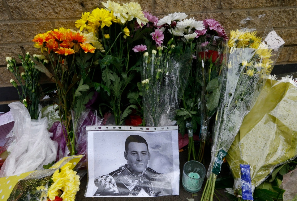 A picture of the murdered 25-year-old soldier Lee Rigby is shown amongst some of the thousands of floral and other tributes left at the scene near Woolwich Barracks in London on May 28, 2013. (AP / Kirsty Wigglesworth)