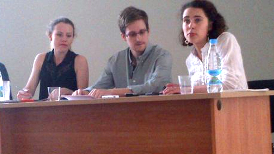 NSA leaker Edward Snowden, centre, attends a press conference at Moscow's Sheremetyevo Airport with Sarah Harrison of WikiLeaks, left, Friday, July 12, 2013. (Human Rights Watch / Tanya Lokshina)