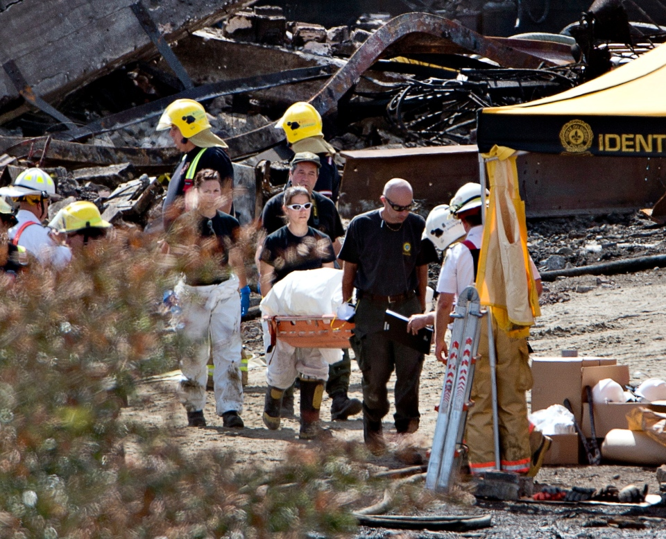 Workers remove remains of a victim in Lac-Megantic, Que., Friday, July 12, 2013. (Ryan Remiorz / THE CANADIAN PRESS)