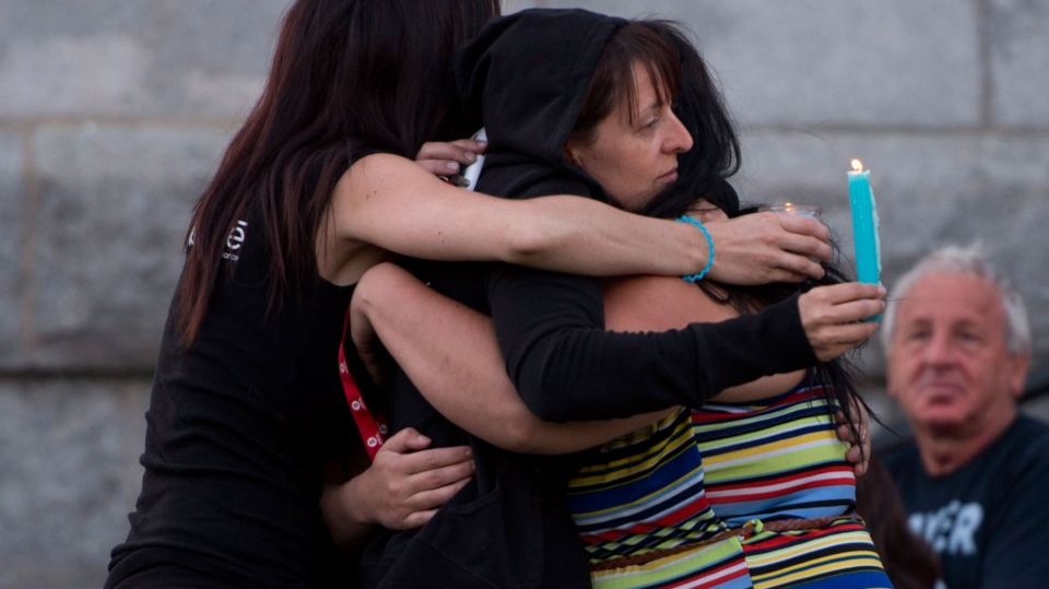 People comfort each other in front of the St-Agnes church during a vigil for the victims of the train crash Lac-Megantic, Que., Friday, July 12, 2013. (Jacques Boissinot / THE CANADIAN PRESS)