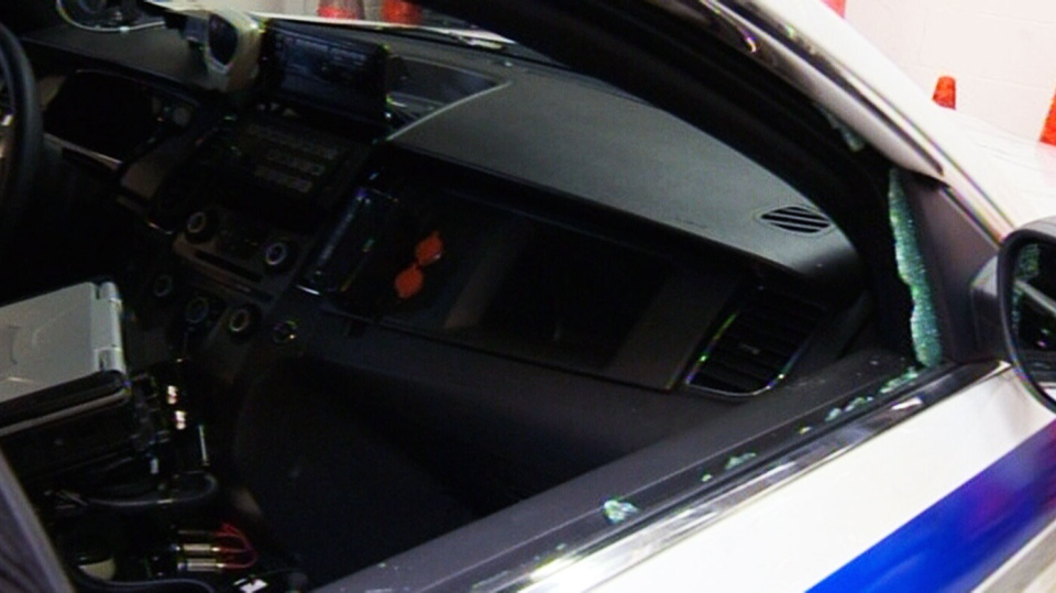 Two men face charges after a Halifax police cruiser was damaged and a briefcase stolen from inside the car.