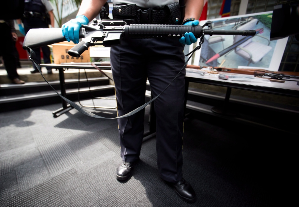 RCMP Cpl. Stephanie Ashton holds an AR-15 assault rifle that was turned in as part of a province-wide gun amnesty program during a news conference in Richmond, B.C., on July 12, 2013. (Darryl Dyck / THE CANADIAN PRESS)