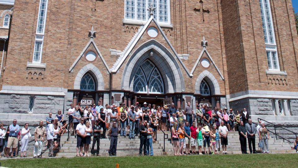 People gather outside as the church's bells chime 50 times for the 50 victims beleived to have died in the train crash blaze in Lac-Megantic, Que., Saturday, July 13, 2013. (Jacques Boissinot / THE CANADIAN PRESS)
