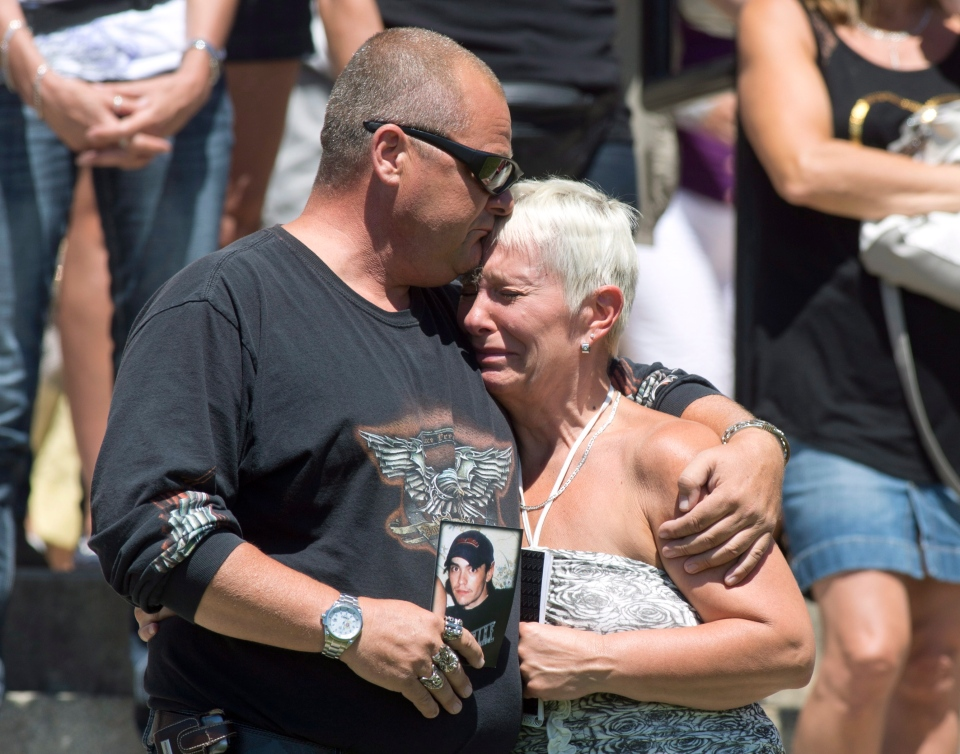 Lise Doyon is comforted by her friend Jeannot Labrecque as the church's bells chime 50 times for the victims of the train crash blaze, in Lac-Megantic, Que., Saturday, July 13, 2013. (Jacques Boissinot / THE CANADIAN PRESS)
