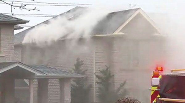 Smoke pours out of a burning Mississauga home where police say evidence of a grow-operation was discovered, Tuesday, April 26, 2011.