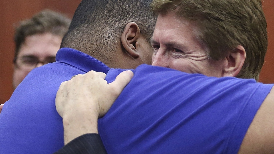 George Zimmerman's Defense attorney Mark O'Mara, right, celebrates with family and friends of George Zimmerman after Zimmerman's not guilty verdict was read in Seminole Circuit Court in Sanford, Fla. on Saturday, July 13, 2013. (AP / Gary W. Green)