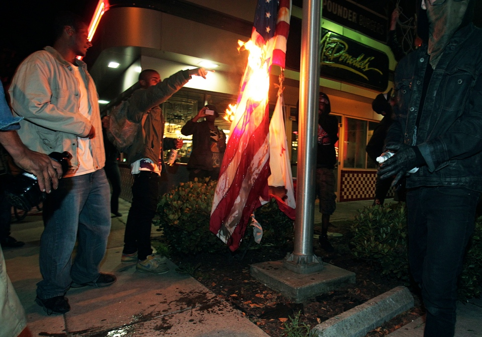 Marchers burn a United States flag outside a fast food restaurant during a protest after George Zimmerman was found not guilty in the 2012 shooting death of teenager Trayvon Martin in Oakland, Calif.,  July 14, 2013. (Bay Area News Group, Anda Chu)
