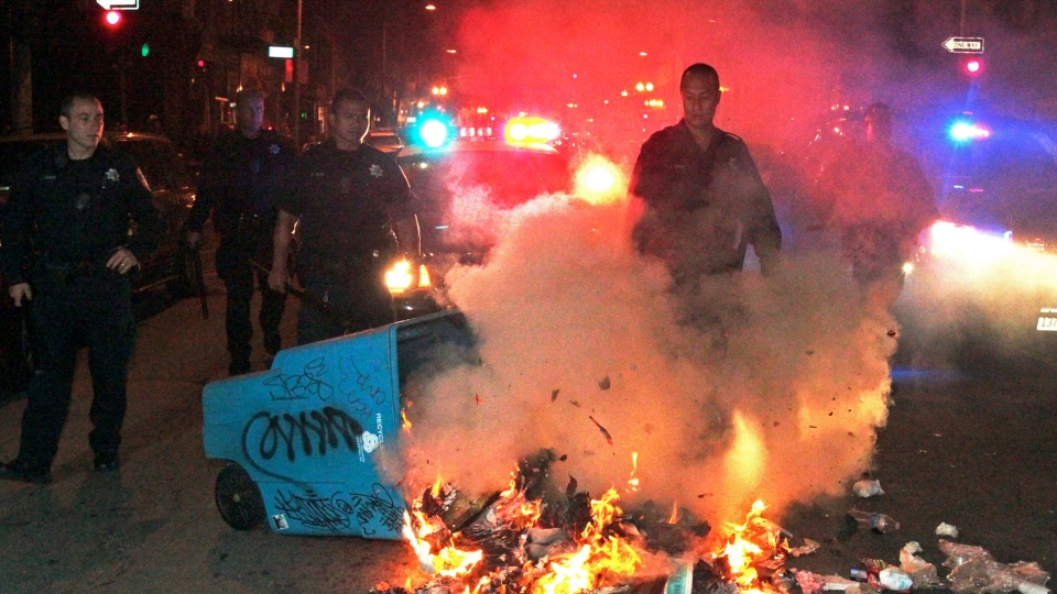 Oakland police officers work to extinguish a fire during a protest after George Zimmerman was found not guilty in the 2012 shooting death of teenager Trayvon Martin, in Oakland, Calif., early Sunday, July 14, 2013.  (Bay Area News Group, Anda Chu)