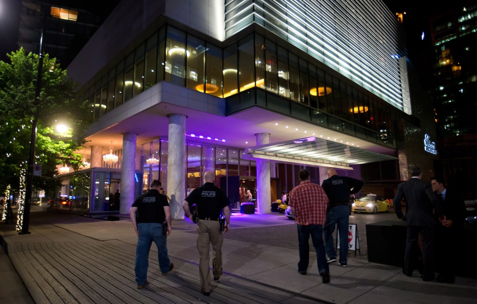 Police officers enter the Fairmont Pacific Rim Hotel where, according to Vancouver Police, Canadian actor Corey Monteith was found dead in a room on July 13, 2013. (Darryl Dyck / THE CANADIAN PRESS)