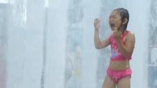 heat wave child in sprinkler