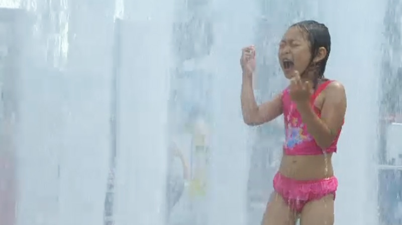A child is seen cooling off in sprinklers on a hot Sunday in downtown Montreal. (CTV Montreal, July 14, 2013)