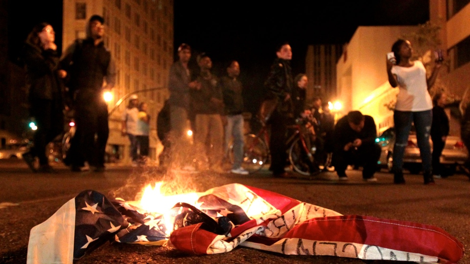 A flag burns during a protest after George Zimmerman was found not guilty in the 2012 shooting death of teenager Trayvon Martin, in Oakland, Calif., early Sunday, July 14, 2013. (Bay Area News Group, Anda Chu)