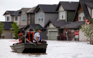 Members of the RCMP return from a boat patrol of a still flooded neighborhood in High River, Alta., Thursday, July 4, 2013. (CP / Jeff McIntosh)